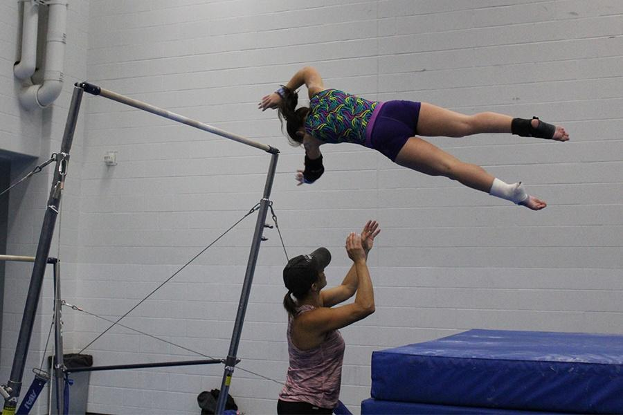 Madison+Mullens+%2812%29+attempts+a+bail+with+the+help+of+Coach+Karen.+She+was+hoping+to+improve+this+skill+before+the+first+meet.