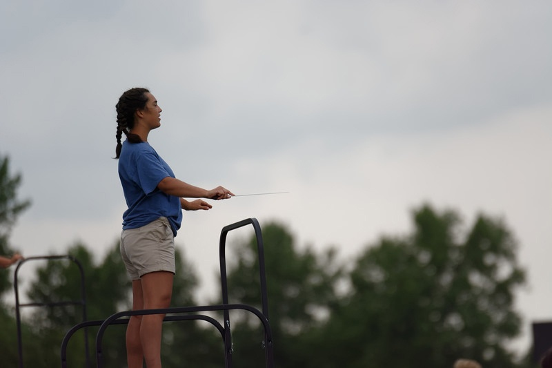 Gianna Rea (11) is standing on top of her drum major podium and is conducting the band. This was Rea's third year in the Tribe of Pride.