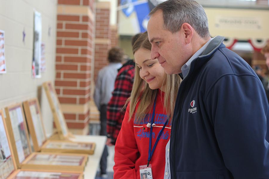 Claire Anton (12) shows her veteran dad Mr. Thomas Clark's, Social Studies, display cases. Mr. Clark and history club members set up the decorations for the ceremony.