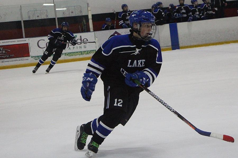 Jayden+Lazowski+%289%29+rapidly+skates+towards+the+puck.+Lazowski+and+other+players+defended+the+player+who+had+it.