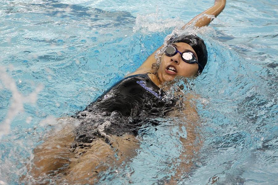 Alexis Casillas (9) swims a backstroke event. The girls took wins in multiple events for each stroke.
