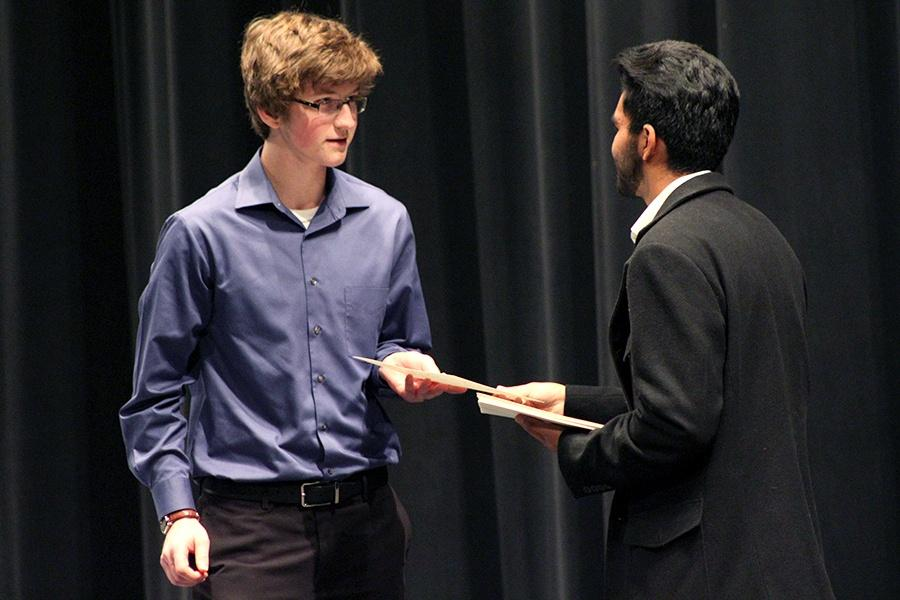Ethan Pinarski (11) accepts his induction certificate from secretary Gurvir Gill (12). Over 100 new members received certificates.