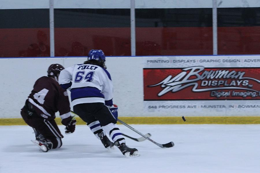 Jason Finley (11) fights against his opponent and races towards the puck. Finely ended up getting to the puck first.