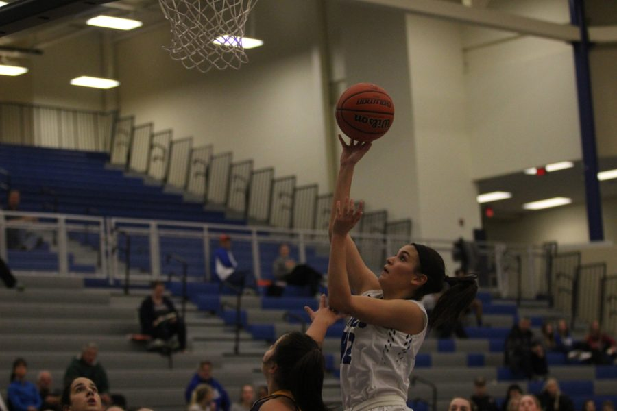 Aubrey Rowser (11) shoots a layup over her opponent. The team had many good drives and played well offensively.
