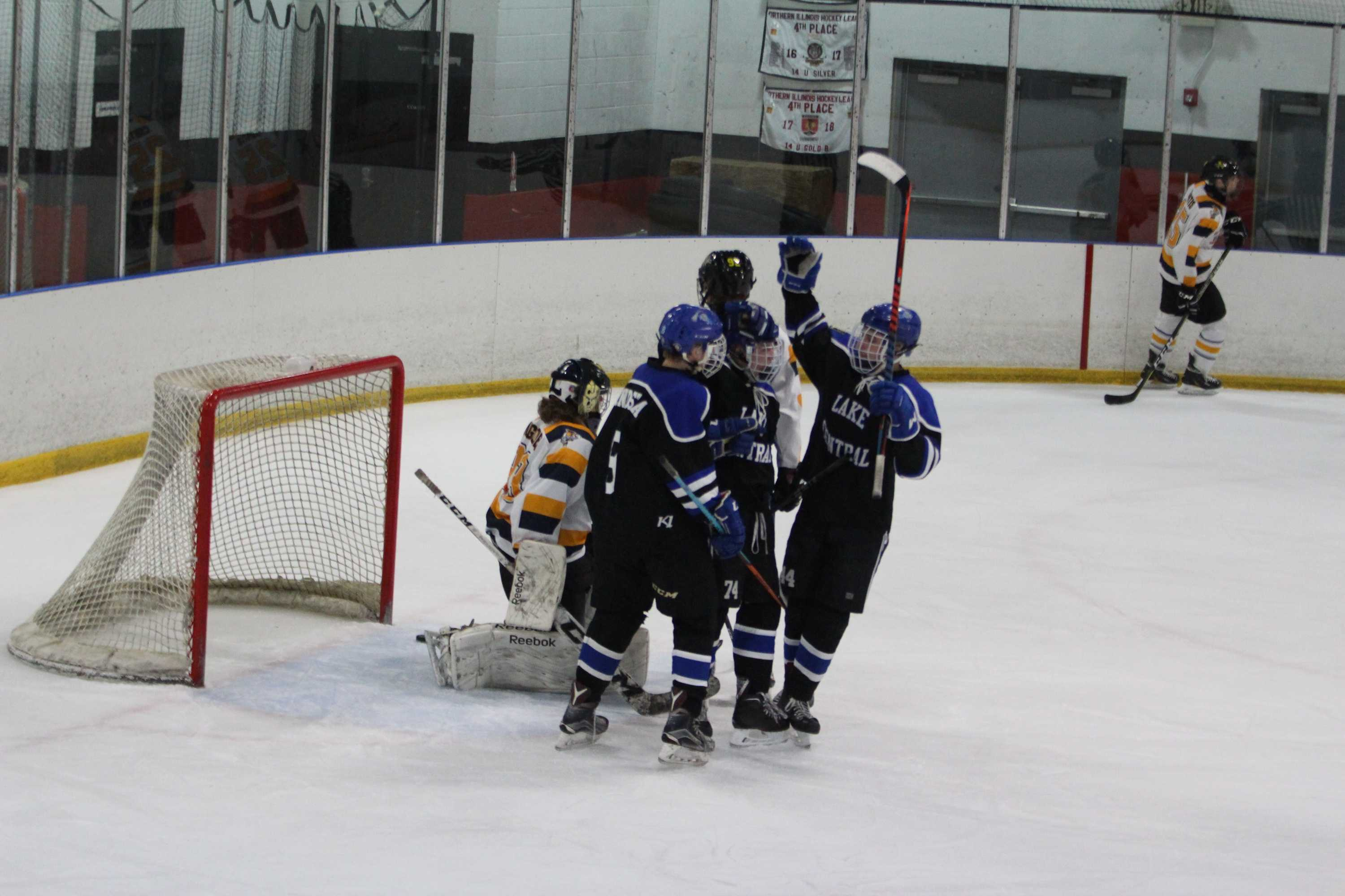 John+Bondi+%2810%29+and+Ryan+Bandstra+%2810%29+congratulate+Kerrick+after+his+first+goal+of+the+night.+Other+players+in+the+student+section+and+on+the+bench+also+cheered.+