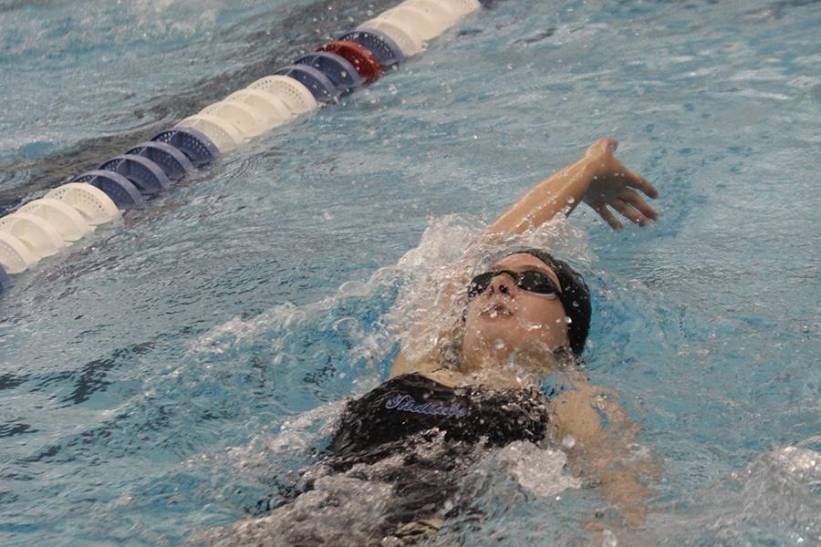 Alyssa Todd (11) swimming the 100 Backstroke in the 11th event of the night. This is Todd's third year on the team. Photo by: Reyna Mahan