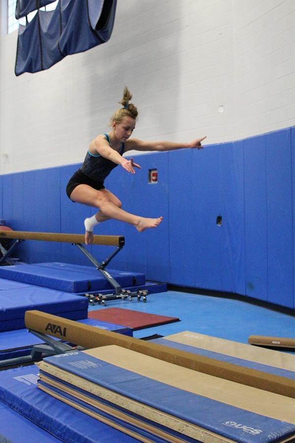 Nicole Wasyliw (10) practices a wolf jump on the low beam. This jump was easier because she had a surgery on her ankle after hurting during gymnastics.