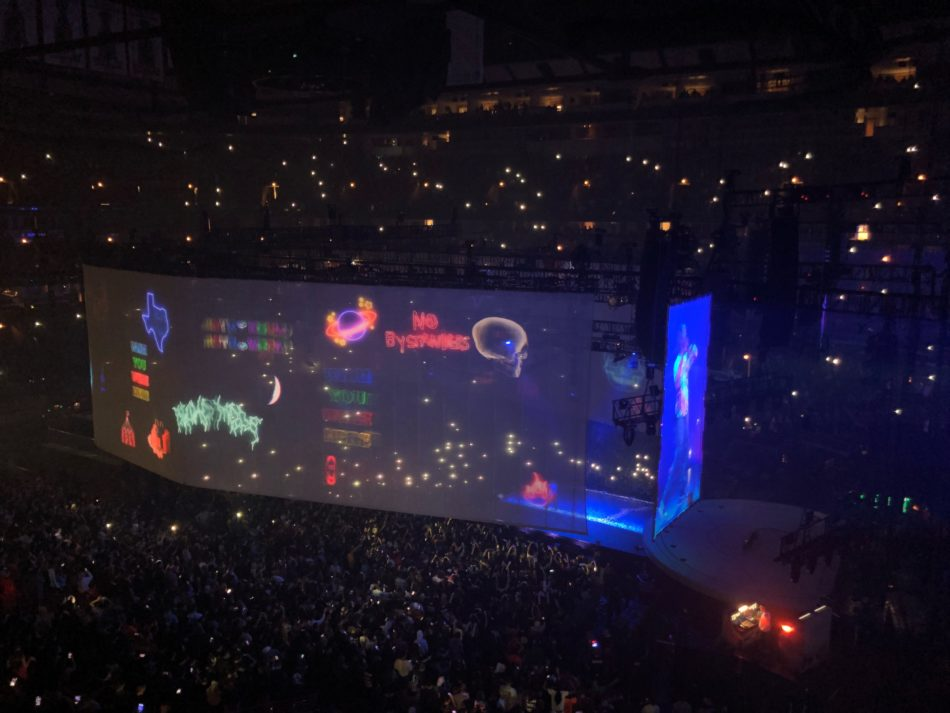 During the concert, a screen is lowered to show different images and visual aids as Travis Scott raps the song