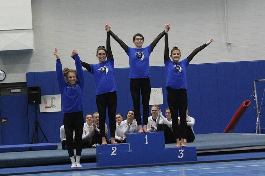 Girls+on+varsity+gymnastics+stand+tall+after+placing+All-Around.+The+team+earned+a+total+points+of+109.15%2C+a+new+school+record.