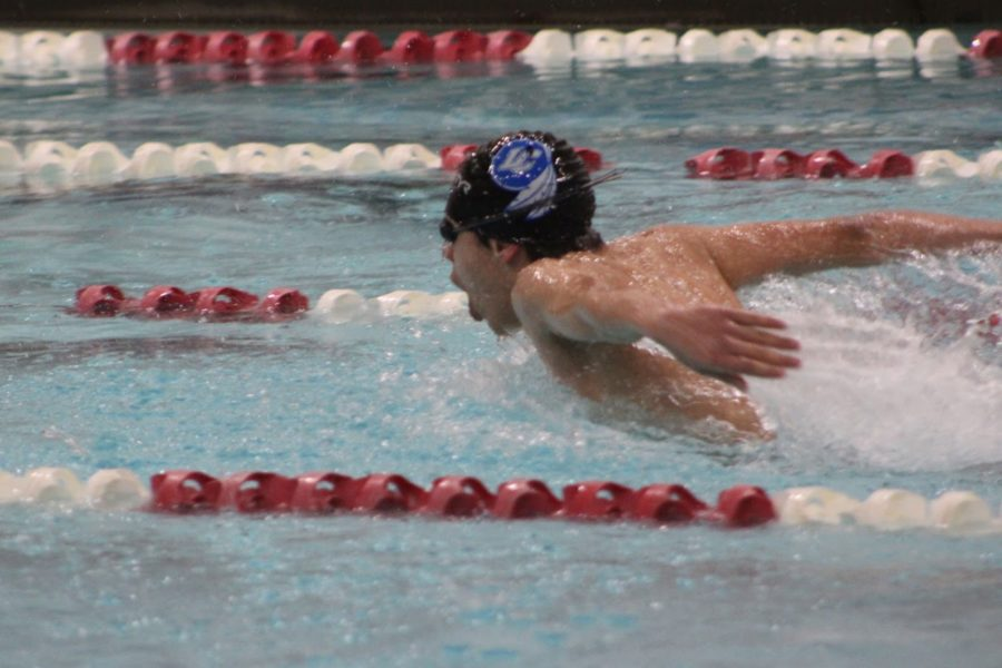 A+swimmer+reaches+out+of+the+water+during+a+race.+The+team+has+been+preparing+to+compete+at+sectionals+in+February.