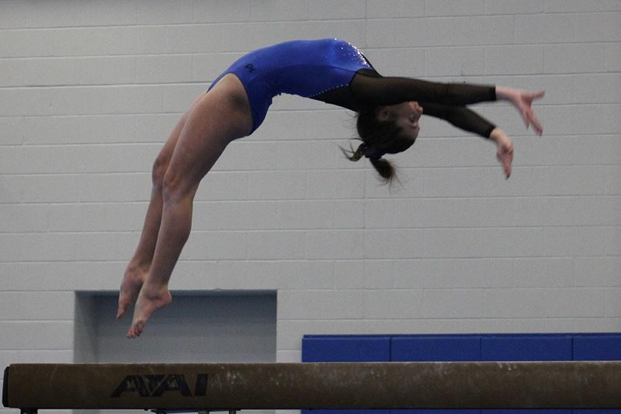 Cloe Amanatidis (9) does a back handspring on beam. This was the last home meet for the team.