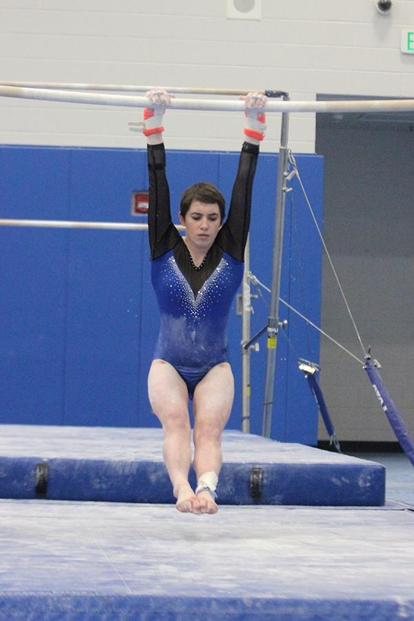Madeline+Bugg+%2810%29+jumps+up+to+grab+onto+the+uneven+bars.+The+team+competed+against+two+schools.+