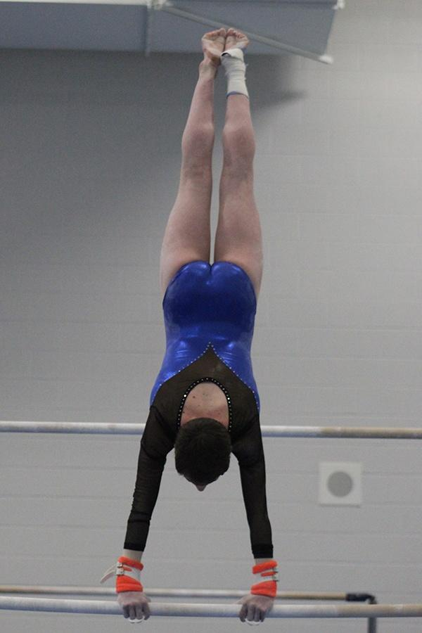 Madeline+Bugg+%2810%29+does+a+handstand+during+her+bars+routine.The+girls+competed+on+Feb.+13.