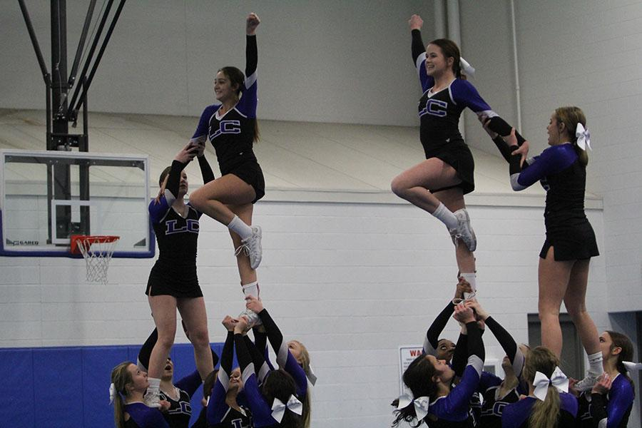 The+flyers+smile+as+their+stunt+groups+hold+them+up.+Cheer+has+traveled+to+Disney+for+the+past+four+years.+