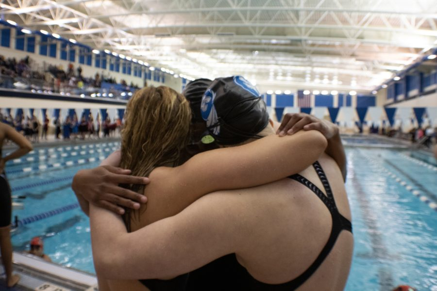 Adisyn Sawaska (10) Jourie Willson (9) Hanna Spoolstra (10) hug after the 400 yard freestyle relay. The girls sat on the first place podium after swimming there best time.