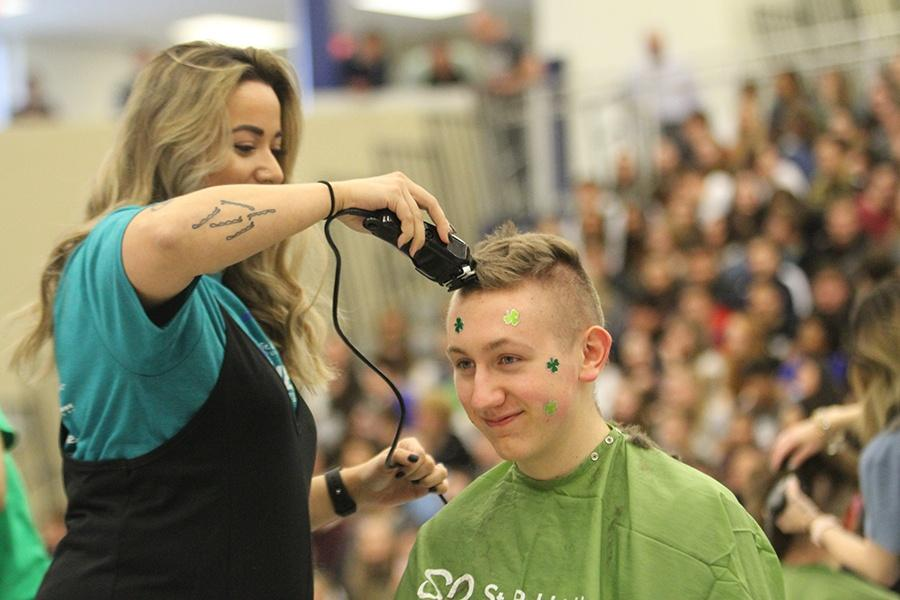 A student gets his hair shaved at the St. Baldrick's event. Thirty-two other volunteers got their heads shaved to raise money and bring awareness to childhood cancer. Photo by: Karisa Candreva