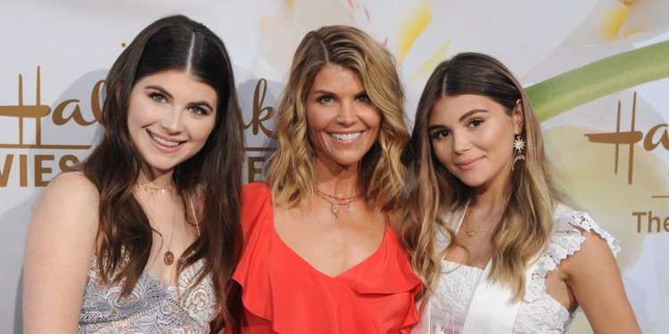 Lori+Loughlin+smiles+with+her+daughters+Olivia+Jade+and+Isabella.+The+family+was+accused+of+paying+%24500%2C000+in+bribes+to+allow+their+daughters+to+attend+USC.