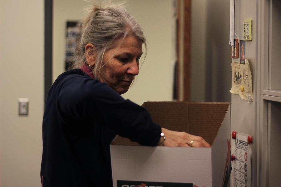 Lori Brumm, main office secretary, packs sentimental items into a box. Brumm worked for the school corporation for 29 years.