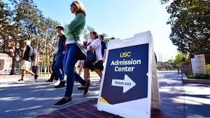 Parents walk past the University of Southern California's admissions board.  The parents, with students, were touring the school after the incident.