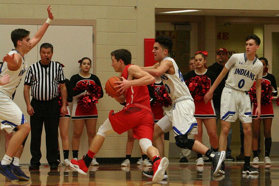 Dominic Ciapponi (12) and Kyle Blum (11) make a team effort in order to stop their opponent from making a shot and scoring. The boys, unfortunately, lost to Munster with an ending score of 57-44.