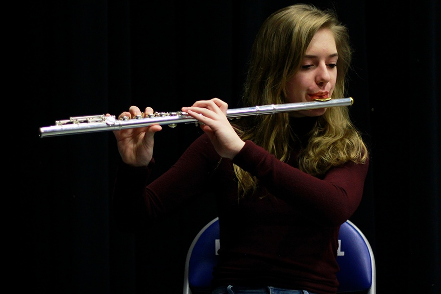 As she sits on the auditorium stage, Emma Westerfield (10) plays familiar tunes on her flute. Westerfield went through extensive interview processes to be considered for the Interlochen summer camp.