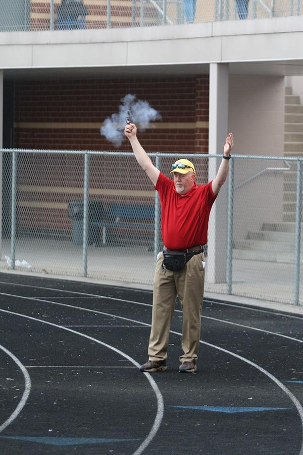 Mr.+Jeff+Rody%2C+Science%2C+shoots+the+starter+gun+to+commence+the+400+meter+dash.+The+meet+was+held+at+home.