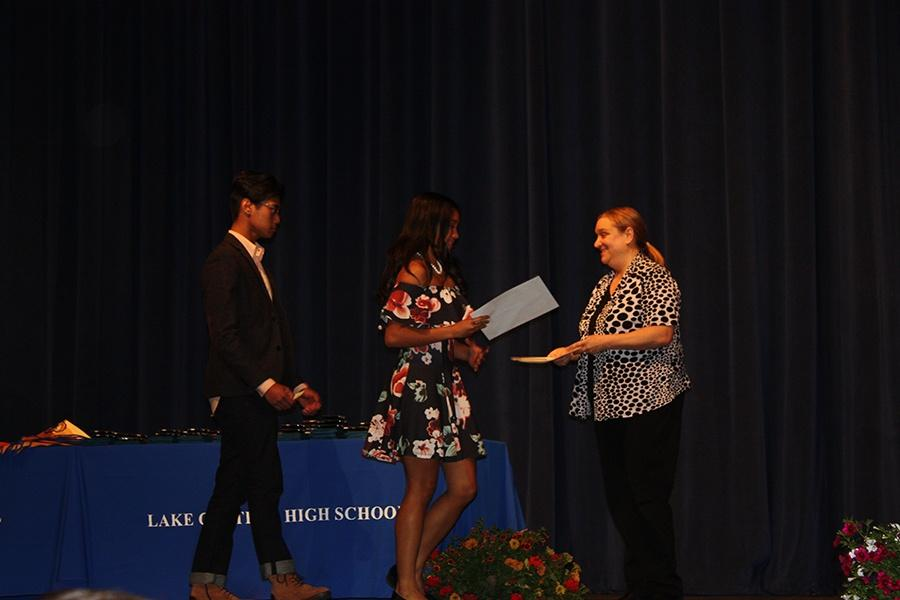 Two seniors walk up the stage to get the money they received for scholarships.  In the auditorium, may seniors walked the stage to receive the money and awards they earned.