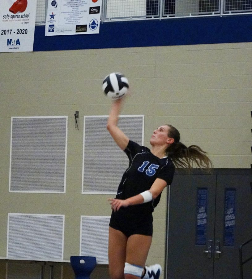Margaret Mulligan (12) serves the ball in the beginning of the game. She earned a point for her team.