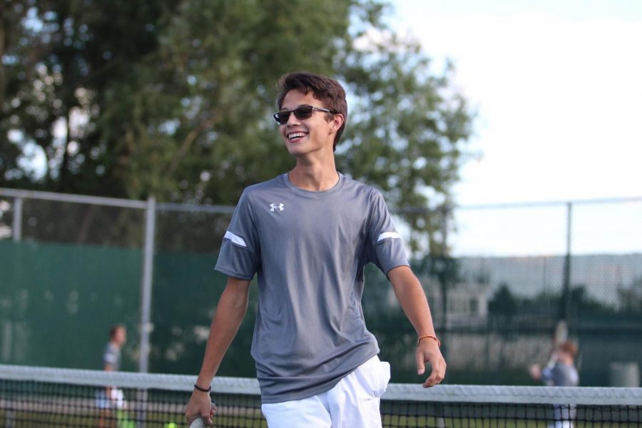 Luis Martinez (11) smiles back at his doubles partner after winning the point against his opponent.  Martinez also won his match against Hanover.