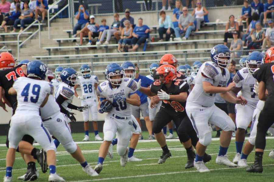 During the running play, Ben Bacso (11) avoids the tackle for a gain up the middle. The boys practiced for eight hours that week.
