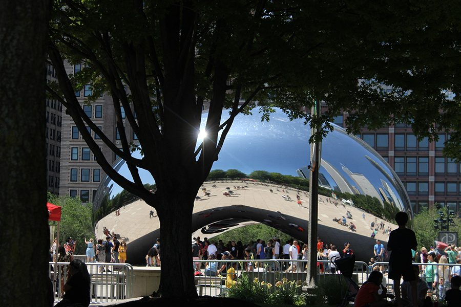 "People gather around Chicago's Bean sculpture. People often look at and take photos with ""The Bean."""