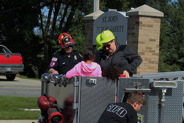 Members of the St. John Fire Department help children into the fire truck's basket. Families at the event got a first-hand look at the equipment and methods used in emergencies.