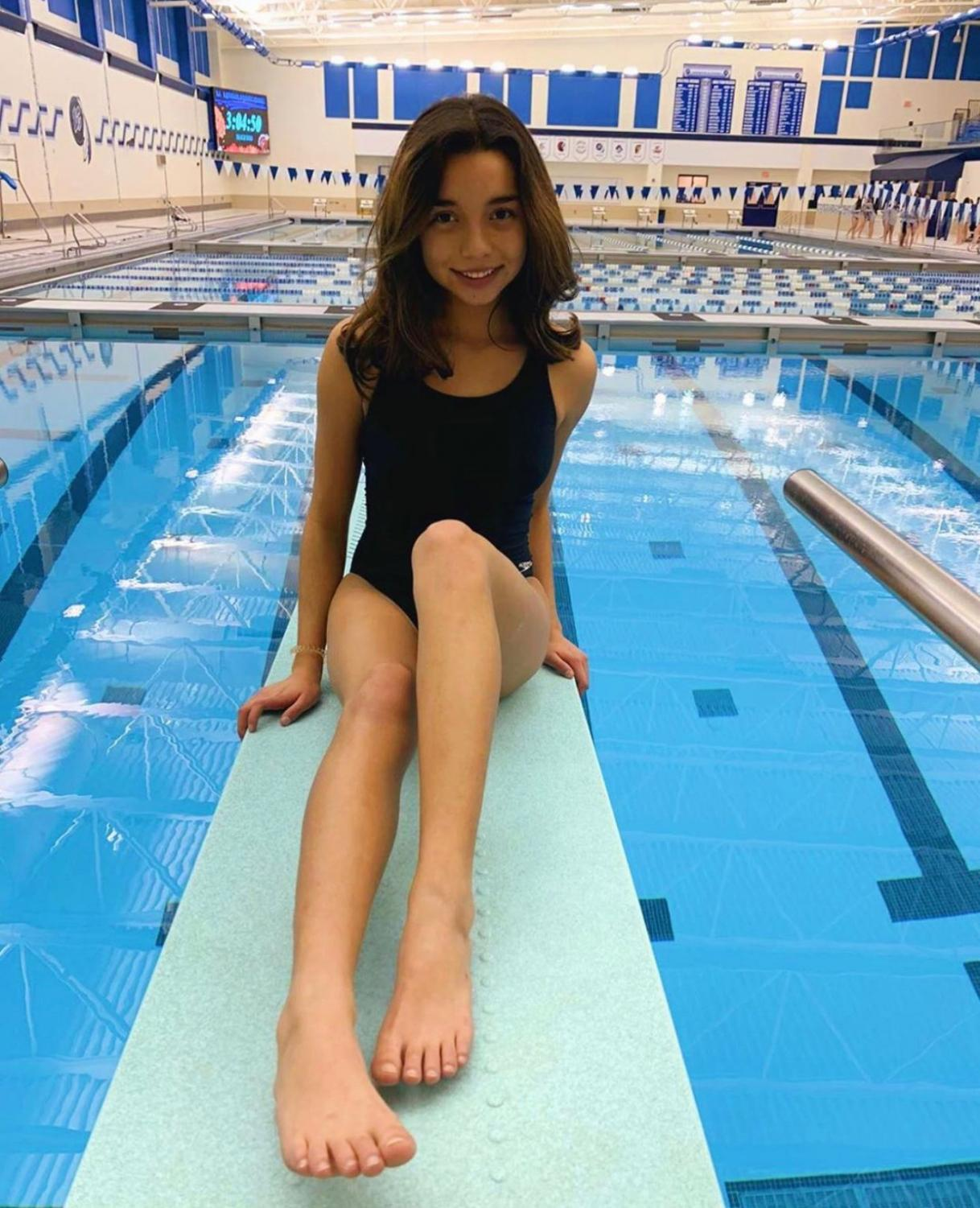 Kayla Garza (10) sits on a diving board after her first meet. She is new to the team and to diving as a sport.