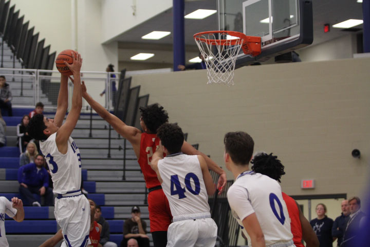 Ami Khatra (12) catches a rebound. Khatra shot the rebound and made the basket.