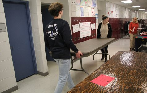 Nathanial Grahovac (12) and Emma Robustelli (11) assist a woman by carrying a heavy table to the opposite end of the school. Many vendors thanked the volunteers for the work they provided.