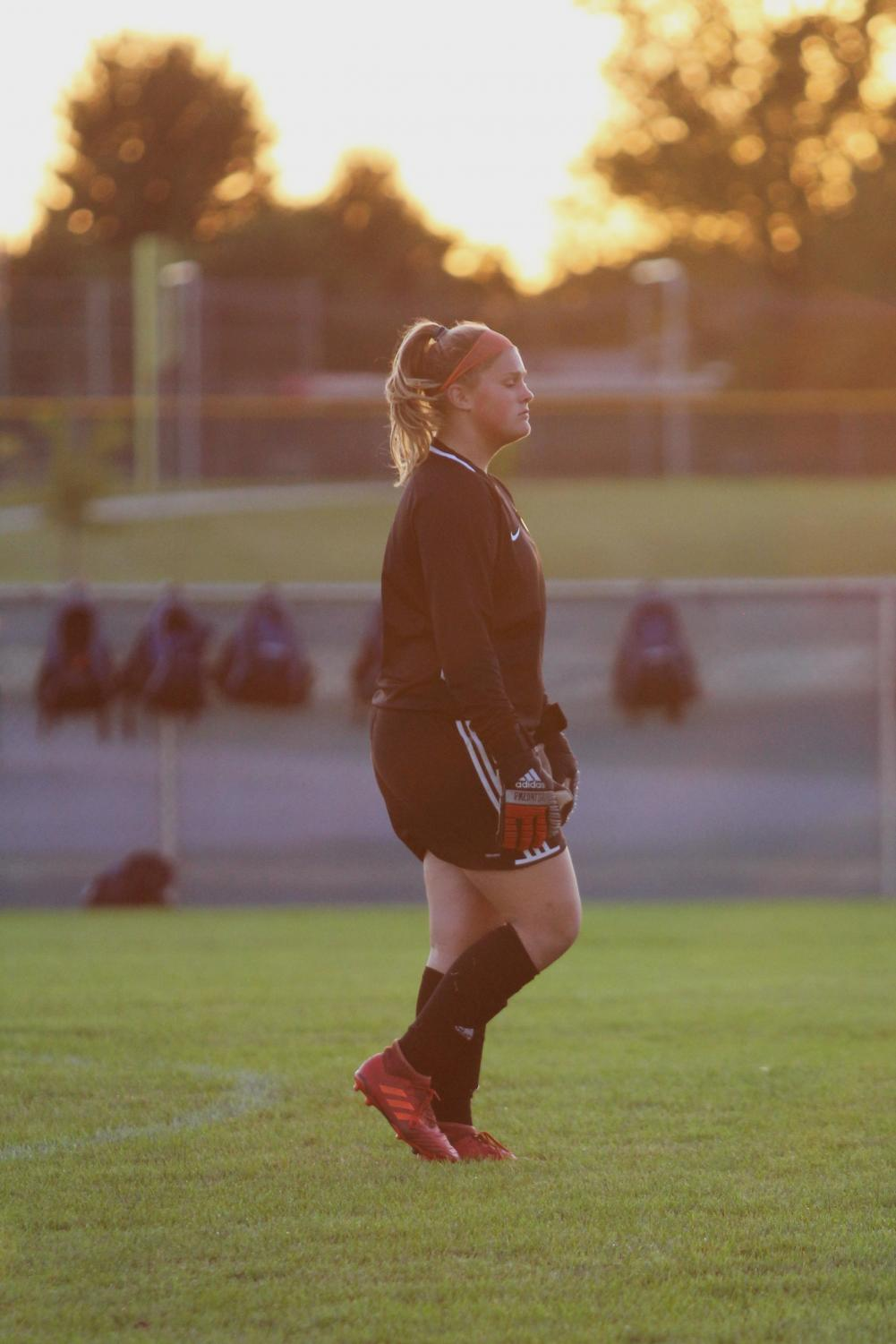 Tatum Damron (11) watches the players anticipating their next move in the first game of the season against Crown Point.  Her determination and skills quickly showed on the field as she protected the net and her team.