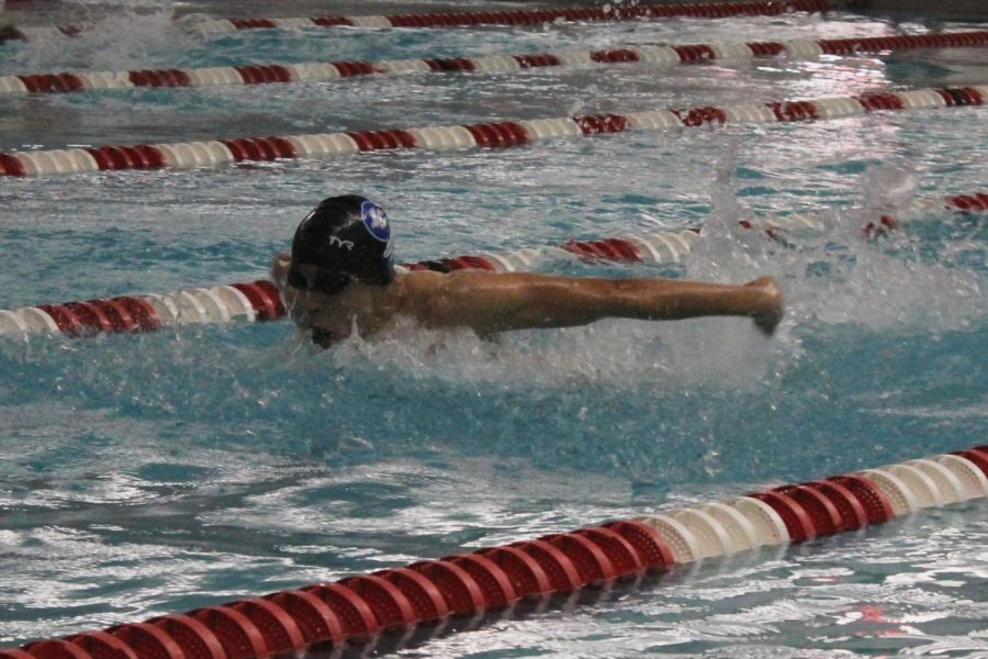 A boys swimmer performs in his event. He finished the race which helped his team place.