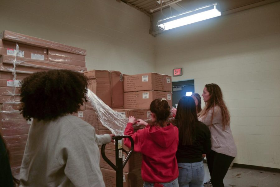 Students+help+unload+the+boxes+of+favors+from+the+storage+room.+The+students+met+on+Wednesday%2C+Jan.+8.