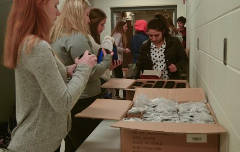 The students concentrate on packing the mugs. To make the process faster, the students worked in groups and created assembly lines at multiple tables.