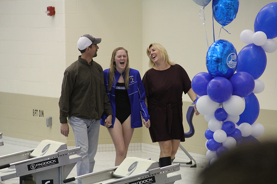 Peyton+Halfeldt+%2812%29+walks+hand+in+hand+with+her+parents+on+her+swim+senior+night.+They+were+laughing+at+the+announcer%E2%80%99s+description+of+her.%0A