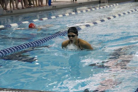 Natalia Mendoza(12) swims to the finish line as she competes in the 100 butterfly.  She is able to beat her competitor.