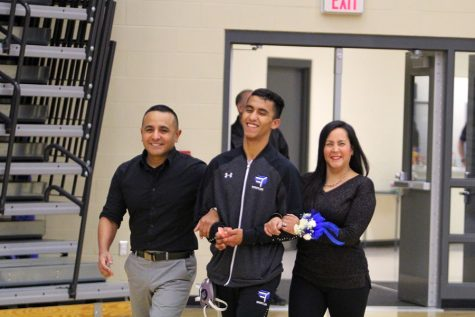 Christopher Cortez  (12) and his parents walk towards his coaches who congratulate him on the four years he committed to wrestling for Lake Central. Jan. 22 was the Varsity team's senior night at Lake Central.