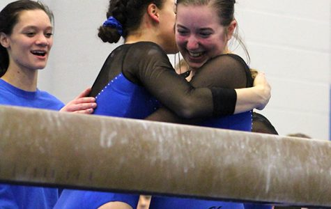 Allison Mybeck (11) rejoices after sticking the landing. Mybeck was embraced by her teammate and received applause.