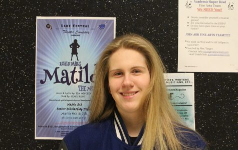 Kayla Longfield (11) smiles in front of a poster for Matilda. Longfield was one of the three student directors of the musical.
