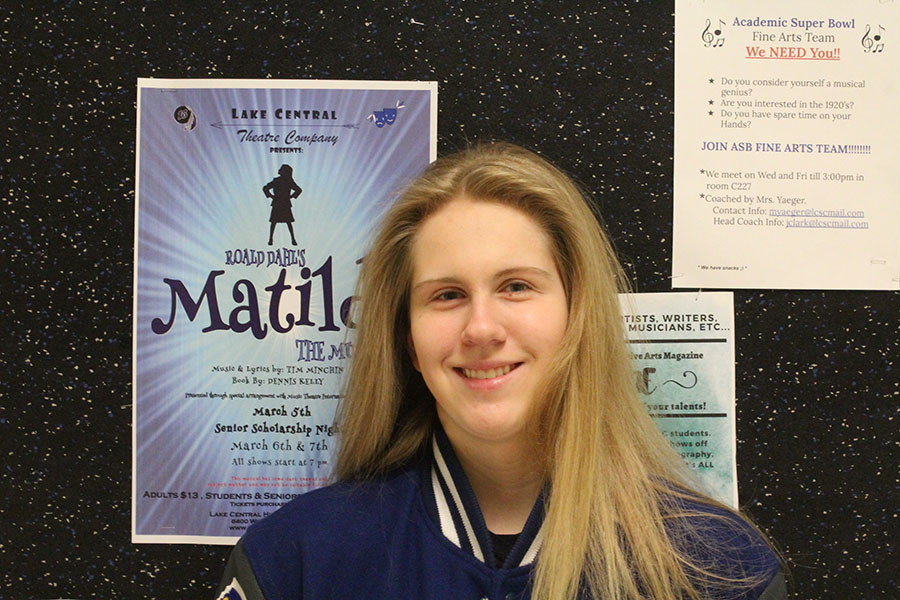 Kayla+Longfield+%2811%29+smiles+in+front+of+a+poster+for+Matilda.+Longfield+was+one+of+the+three+student+directors+of+the+musical.