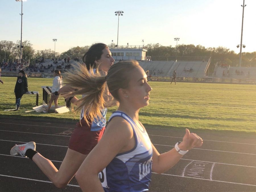 Krista Kulacz (10) runs on the track alongside a member of another team during the 2019 girls track season. The season this year was cancelled, so there will be no meets or practices.