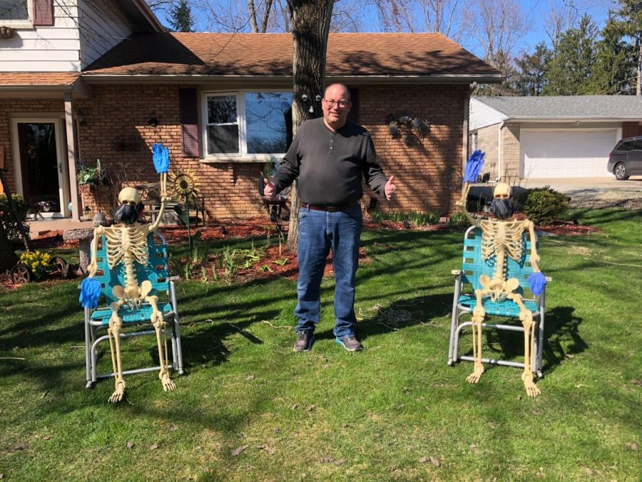 Madison Zielke's (11) dad, a paramedic for Superior, poses with the decorations in front of their house. He's giving a friendly reminder to everyone that drives by to wear masks and gloves and to stay safe.