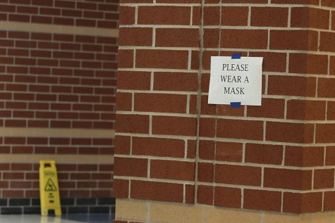 "A ""Please Wear a Mask"" sign hands in Main Street in the high school. There are signs up all around the school reminding students and staff to social distance and wear their masks."