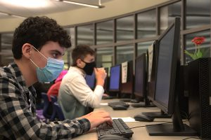 Students sit in the computer lab working on assignments for class. They all have to wear masks in order to follow social distancing guidelines.