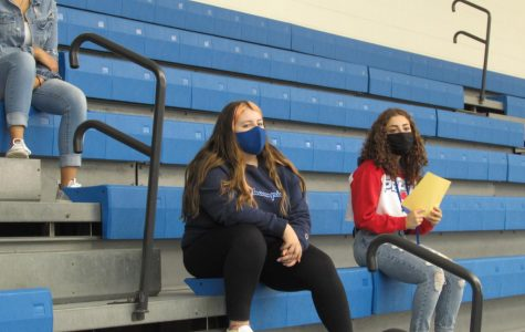 Amahlia Rodriguez (12) and Mathilda Geyer (11) listen to the coaches speak. They attended the meeting on the pool balcony to find out more information about the swimming and diving teams.
